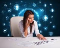 Affärskvinnasammanträde på skrivbordet med sociala nätverkssymboler Arkivfoto