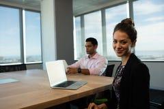 Affärskvinnasammanträde på tabellen med den manliga kollegan i bakgrund Arkivbild