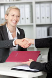 AffärskvinnaShaking Hands With kandidat på skrivbordet royaltyfri fotografi