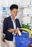 AffärskvinnaSmiling While Buying produkter från apotek arkivfoto