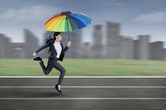 Affärskvinnaspring med det färgrika paraplyet Royaltyfri Bild