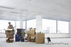 AffärskvinnaUnpacking Cartons In kontor Arkivfoton