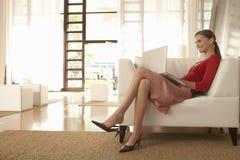 AffärskvinnaUsing Laptop While sammanträde på lobby för stol i regeringsställning Royaltyfri Fotografi