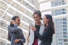 Affärskvinnavänner som håller ögonen på video på en smartphone Arkivbild