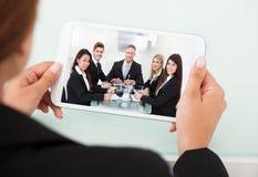 Affärskvinnavideoconferencing med laget på den digitala minnestavlan Royaltyfri Foto