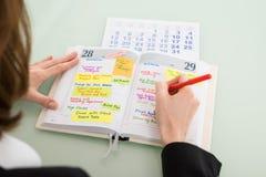 AffärskvinnaWith Calendar Writing schema i dagbok Arkivbild