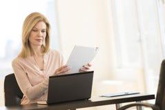 AffärskvinnaWith Laptop Holding meritförteckning i regeringsställning Royaltyfri Foto