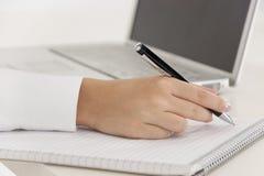 Affärskvinnawriting på en anteckningsbok arkivfoto