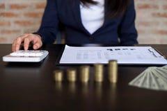 Affärskvinnor beräknar inkomsten från exportaffären på trätabellen äganderätt för home tangent för affärsidé som guld- ner skyen  arkivbilder