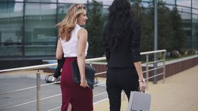 Affärskvinnor går mot bakgrunden av en affärsmitt med mappar för legitimationshandlingar Två flickor i strikta dräkter _ arkivfilmer