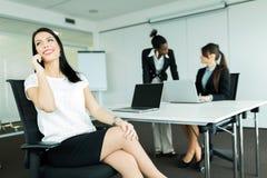 Affärskvinnor i ett kontor som arbetar på en bärbar dator och kallar, poten Arkivfoton