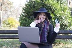 Affärskvinnor i parkera som köper en bärbar dator Arkivbild