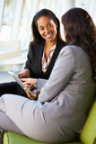 Affärskvinnor med Digital Tabletsammanträde i modernt kontor Fotografering för Bildbyråer