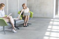 Affärskvinnor med digitalt minnestavla- och bärbar datorarbete på kontoret royaltyfri foto