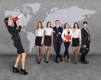 Affärskvinnor med megafonen som framme står av andra affärspersoner Arkivfoton