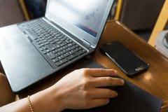 Affärskvinnor räcker arbete med bärbara datorn och musen Arkivbild