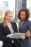 Affärskvinnor som använder den Digital minnestavlan utanför kontor Arkivfoto