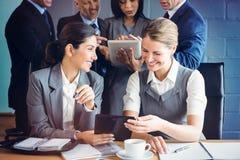 Affärskvinnor som använder den digitala minnestavlan i konferensrum royaltyfri fotografi