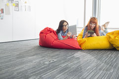 Affärskvinnor som använder digitala minnestavlor, medan koppla av på sittkuddestolar i idérikt kontor Arkivfoto