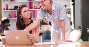Affärskvinnor som arbetar på bärbara datorn i upptaget kontor arkivfilmer