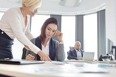 Affärskvinnor som diskuterar över projekt med den manliga kollegan i bakgrund på kontoret Royaltyfri Bild