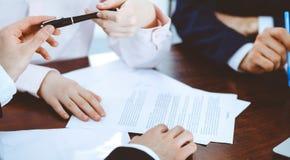 Affärskvinnor som ger en penna till affärsmannen för kontraktskrivning Överenskommelse på förhandling eller mötet bollar dimensio arkivbild