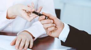 Affärskvinnor som ger en penna till affärsmannen för kontraktskrivning Överenskommelse på förhandling eller mötet bollar dimensio royaltyfria foton