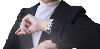 Affärskvinnor som håller ögonen på tid på hennes armbandsur arkivfoto