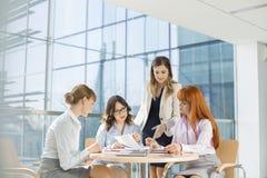Affärskvinnor som i regeringsställning arbetar på tabellen arkivbild