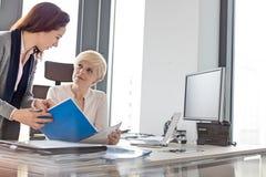 Affärskvinnor som i regeringsställning diskuterar över nytt projekt på skrivbordet fotografering för bildbyråer