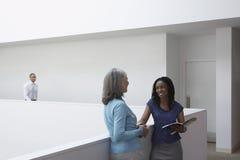Affärskvinnor som i regeringsställning talar hallet arkivfoto