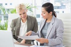 Affärskvinnor som läser mappar royaltyfri bild