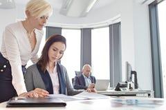 Affärskvinnor som läser projekt med den manliga kollegan i bakgrund på kontoret Arkivfoton