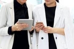 Affärskvinnor som möter, affärskvinnor som använder minnestavlaPC och, ilar telefonen för diskuterar projekt Arkivbilder