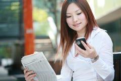 affärskvinnor som rymmer mobil newspaeravläsning Royaltyfria Bilder