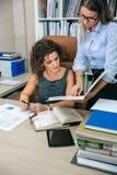 Affärskvinnor som ser dokument i mapp i kontoret Arkivfoto