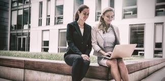 Affärskvinnor som sitter och använder bärbara datorn Royaltyfri Foto