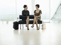Affärskvinnor som sitter på flygplatslobbyen Royaltyfri Fotografi