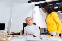 Affärskvinnor som talar och ler, medan granska ett arbetsplan royaltyfri foto