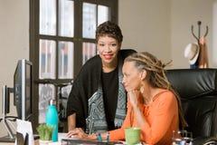 Aff?rskvinnor som tillsammans arbetar i ett id?rikt kontor arkivbild
