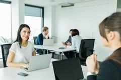 Affärskvinnor som utbyter tankar i en trevlig kontorsmiljö Fotografering för Bildbyråer