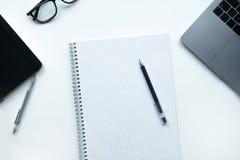 Affärslägenheten lägger: skrivbord med anteckningsboken, blyertspenna, exponeringsglas, bärbar dator på den vita tabellen royaltyfria bilder
