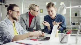 Affärslag av ungdomarsom tycker om att arbeta tillsammans, millennialsgrupp som talar ha gyckel i det hemtrevliga kontoret som är arkivfilmer