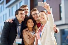 Affärslag med konferensemblem som tar selfie royaltyfri bild