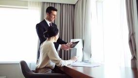 Affärslag med legitimationshandlingar och minnestavlaPC på hotellet lager videofilmer