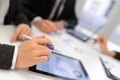 Affärslag som använder minnestavladatoren för att arbeta med finansiella data Arkivfoto