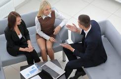 Affärslag som diskuterar finansiella dokument som sitter i lobbyen av kontoret Royaltyfri Foto