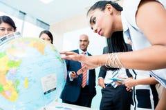 Affärslag som diskuterar globala utbyggnadsplaner arkivfoto