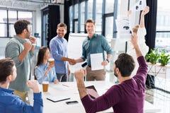 Affärslag som firar framgång tillsammans på arbetsplats i regeringsställning arkivfoto