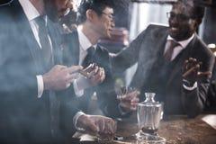 Affärslag som spenderar tid, röker cigarrer och dricker whisky royaltyfri fotografi